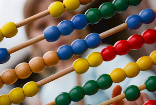 An abacus with beads of several colours, with an out-of-focus face in the background.