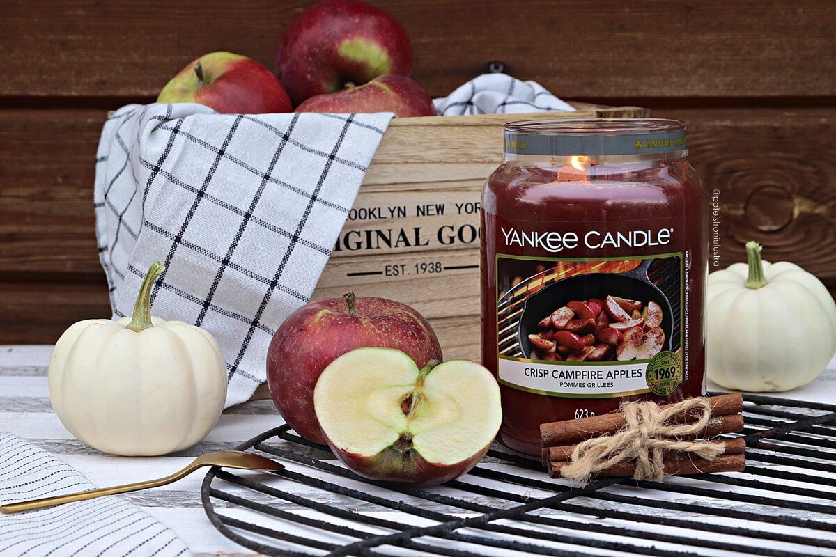 duża świeca yankee candle crisp campfire apples na tle skrzynki z jabłkami