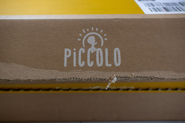 A close up of the opening section of a cardboard box with the Piccolo logo on