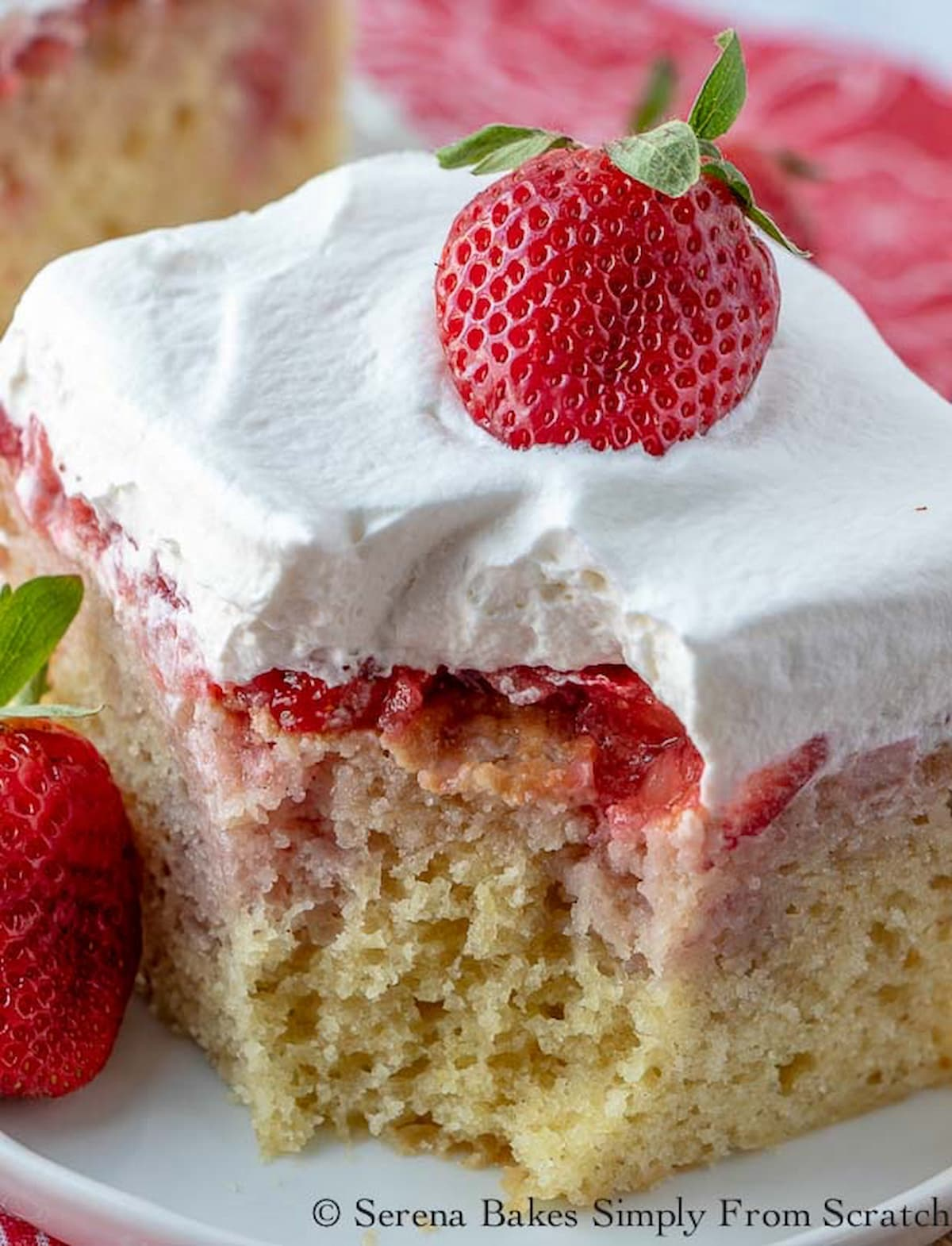 A slice of Strawberry Shortcake Poke Cake on a white plate with a fork full missing.