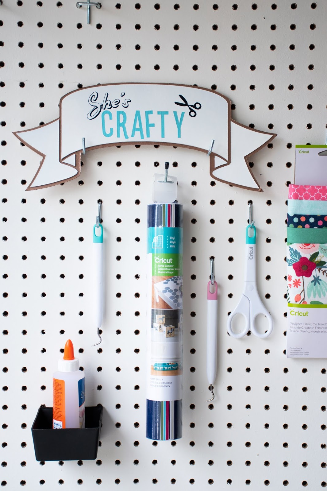 She's Crafty DIY Chipboard Sign on Craft Room Pegboard