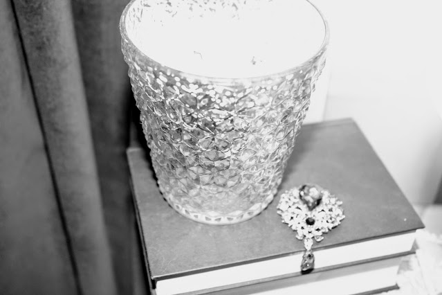Stacked books, mercury glass candle with brooch on books