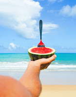 An hand extended out and holding a piece of watermelon. There is a beach and water in the background.