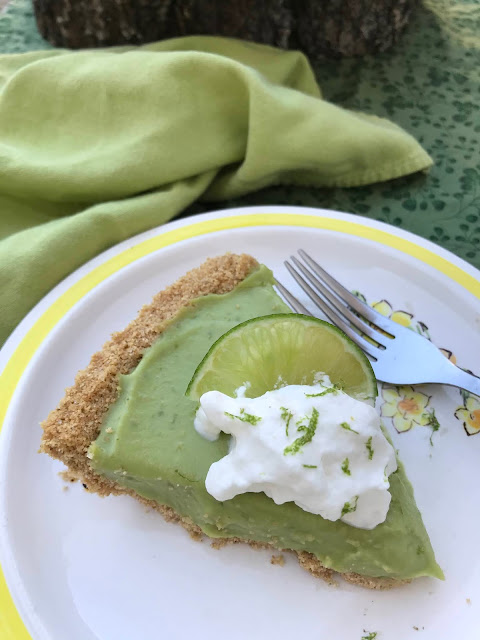 Close up of a slice of lime avocado coconut pie with whipped cream.