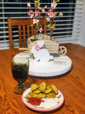 oak table with green glass chalice and a plate arranged with ketchup, light ranch salad dressing, and broccoli tots. behind is a nice spring setting with a wooden bunny and pink flowers.