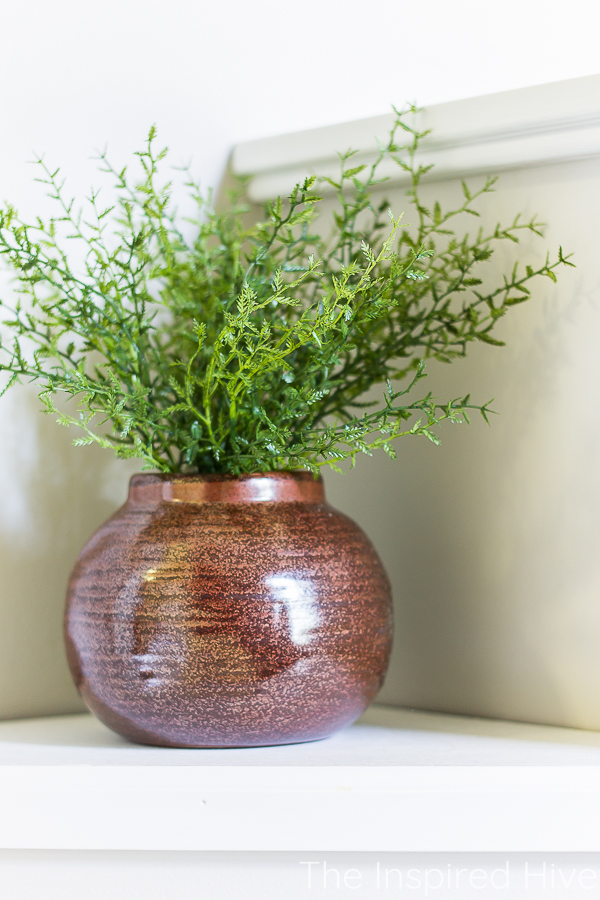 Maroon rust colored vase with greenery