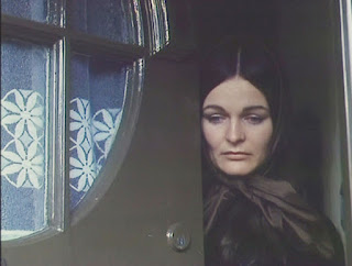 Still from Bleak Moments - woman opening front door of house