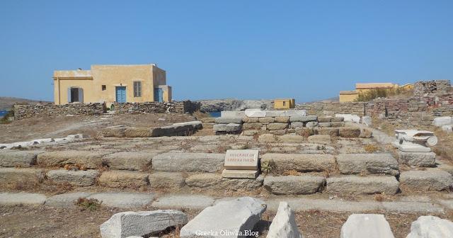 dom w kolorze słonecznego piasku, bezchmurne błękitne niebo, ruiny świątyni Dwunastu Bóstw