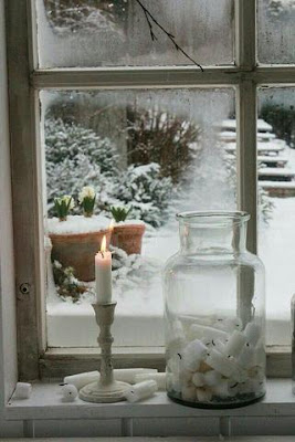 A lit candle next to a glass jar of candle stubs on a windowsill looking out onto a wintry yard.