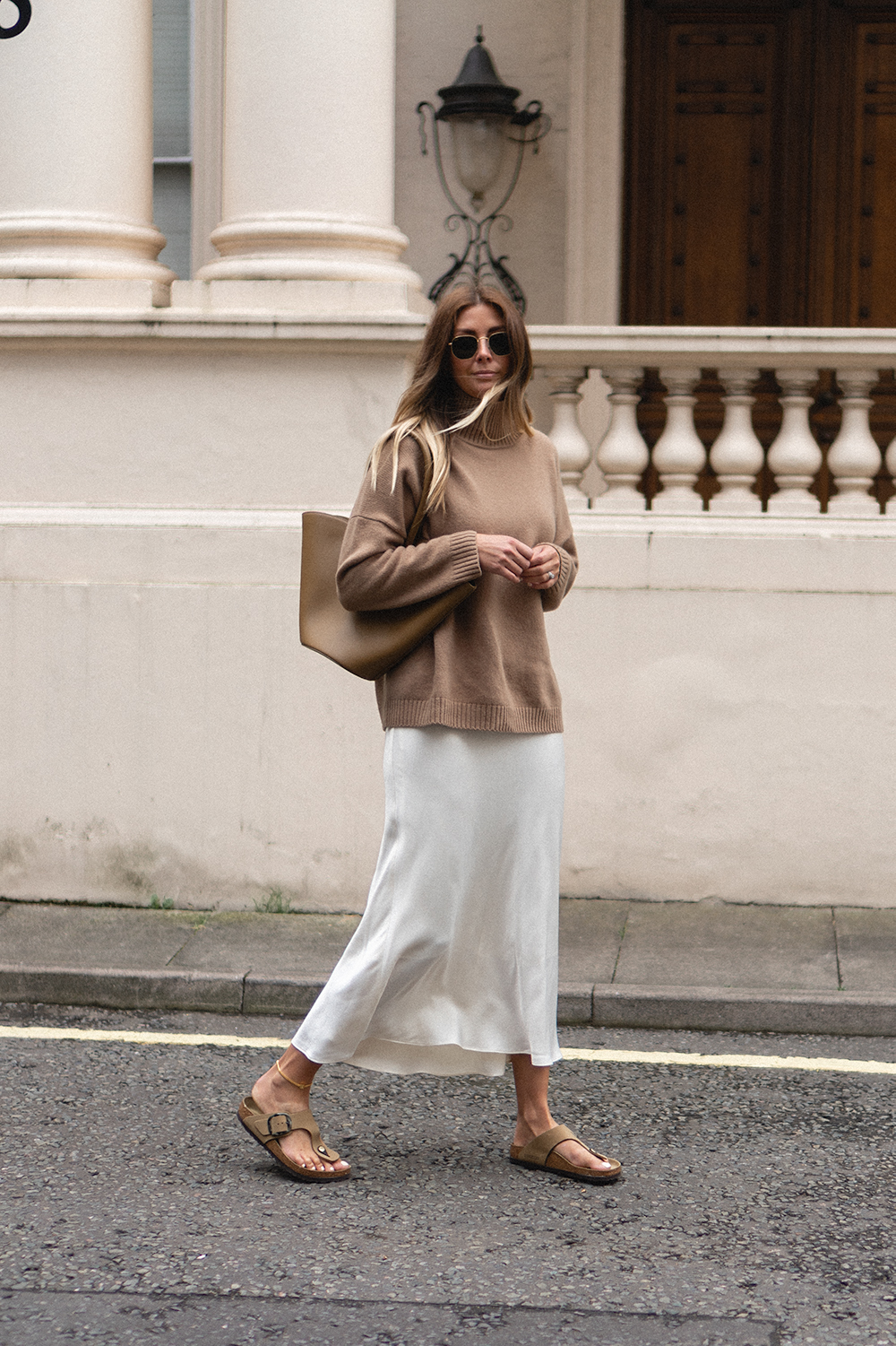 Cozy-Chic Fall Outfit Idea from Birtish Influencer Emma Hill in a Neutral Turtleneck Sweater, Minimalist Tote Bag, White Slip Skirt, and Tan Birkenstock Sandals