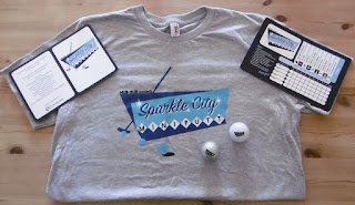 Photo of the Sparkle City Mini Putt t-shirt, minigolf balls and scorecards