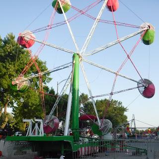 a colorful ferris wheel spins at the North Iowa Fair in Mason City, IA