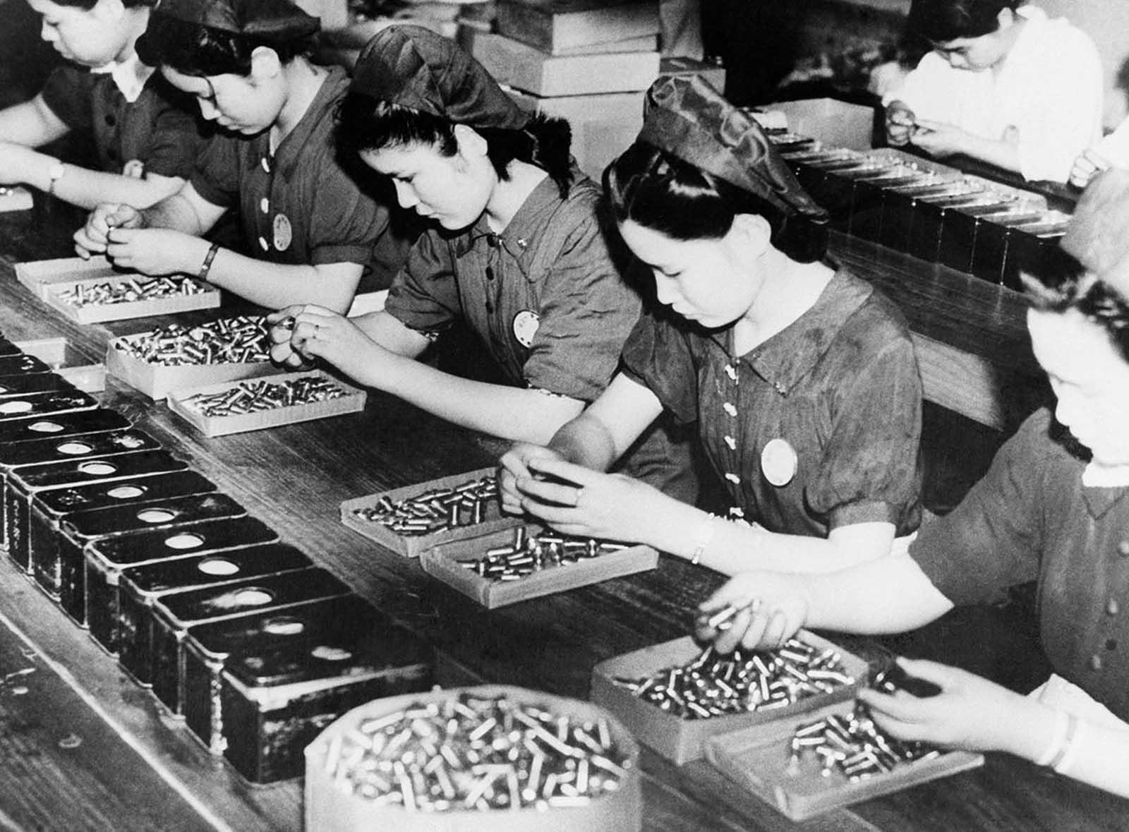 Las mujeres japonesas buscan posibles fallas en las conchas vacías en una fábrica en Japón, el 30 de septiembre de 1941.
