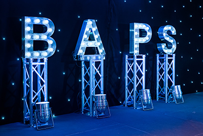 stage set with 4 pillars, each one with a capital letter full of lightbulbs on spelling out BAPS
