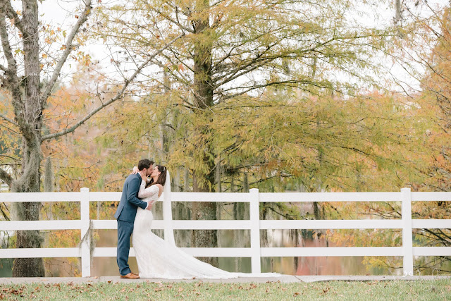 bride and groom kissing in front of fence