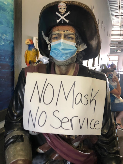 """Statue  of pirate with facemask put on it. Sign attached to it: """"No Mask No Service"""""""