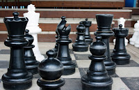 Large toddler-sized chess pieces on a giant chess board