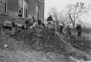 A black and white photograph of a group of men digging in dirt outside a building.