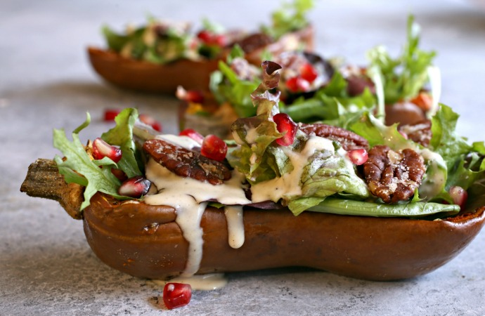 Recipe for salad served inside a roasted honeynut squash and topped with pomegranate arils, candied pecans and a tahini dressing.