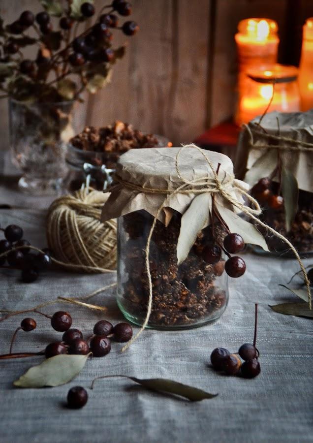 Tarros regalo granola ferrero rocher sin gluten, fondo madera vieja, hojas eucalipto y ramas secas decorativas, cordón de esparto, velas encendidas