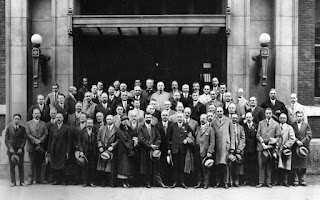 A large group of men and one woman pose in front of a building