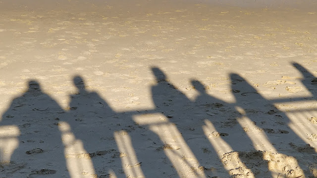 shadows of people along the Thames