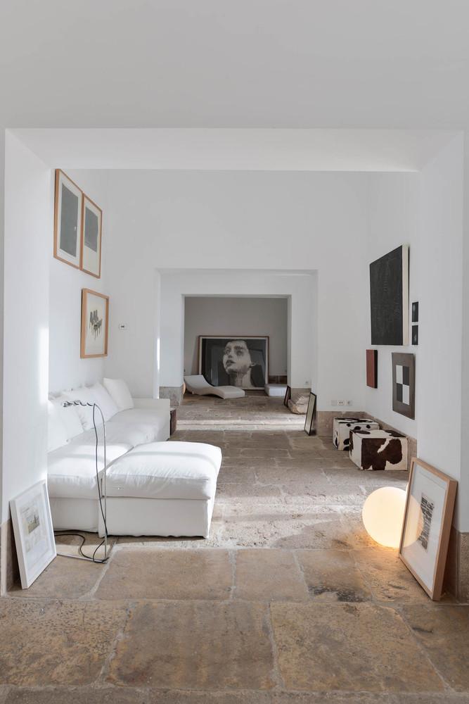 Salón espectacular con sofá blanco, suelo de piedras y cuadros de arte