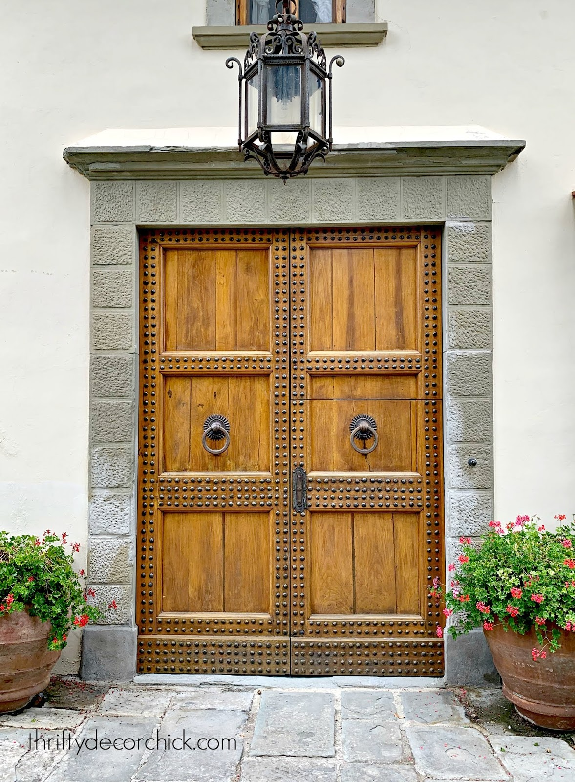 Tuscan wood doors with large metal light and pottery