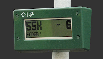 [Image: Photo of a rugged LCD display mounted on a metal pole, displaying the text '55K FORSBY ~6' and stamped with the logo 'HSL HRT'.]
