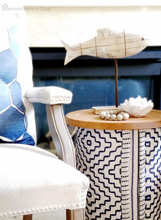 tree stump wrapped up with rug - fish decor on table - lotus lamp, white chair with repurposed jeans pillow