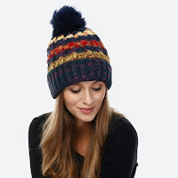 navy blue thick and cozy winter hat with yellow, cream, and red stripes and a big pompom