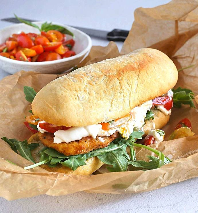 Recipe for a sandwich with a breaded veal cutlet, arugula, tomato salad and burrata cheese, drizzled with balsamic vinegar.
