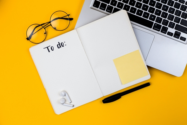 "Flatlay home office fundo amarelo notebook, óculos e um caderno sem pauta escrito ""to do"""