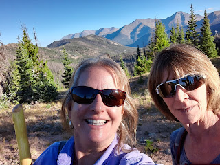 Two ladies hiking with a view of the mountains.