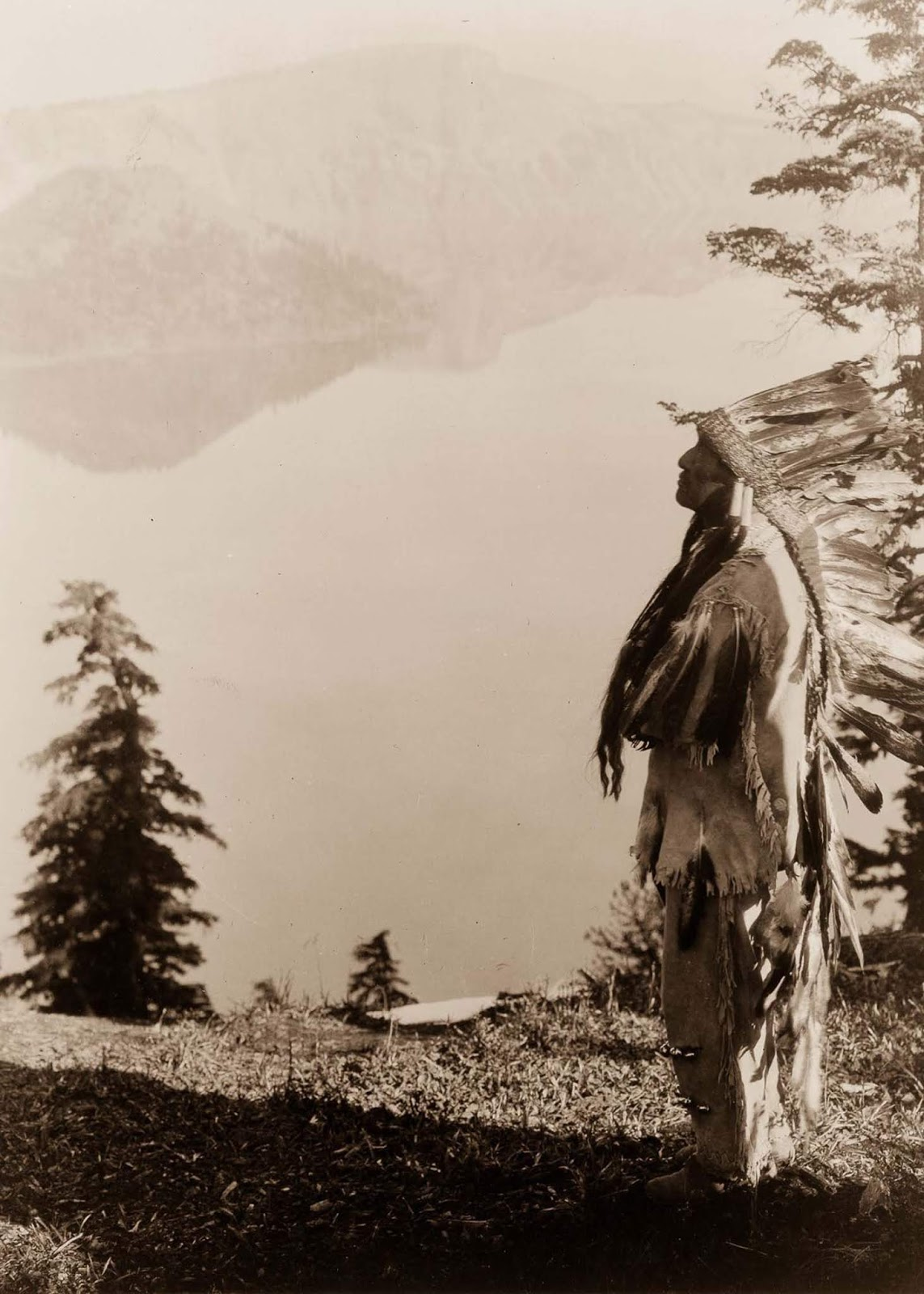 A Klamath chief stands on a hill above Crater Lake, Oregon. 1923.
