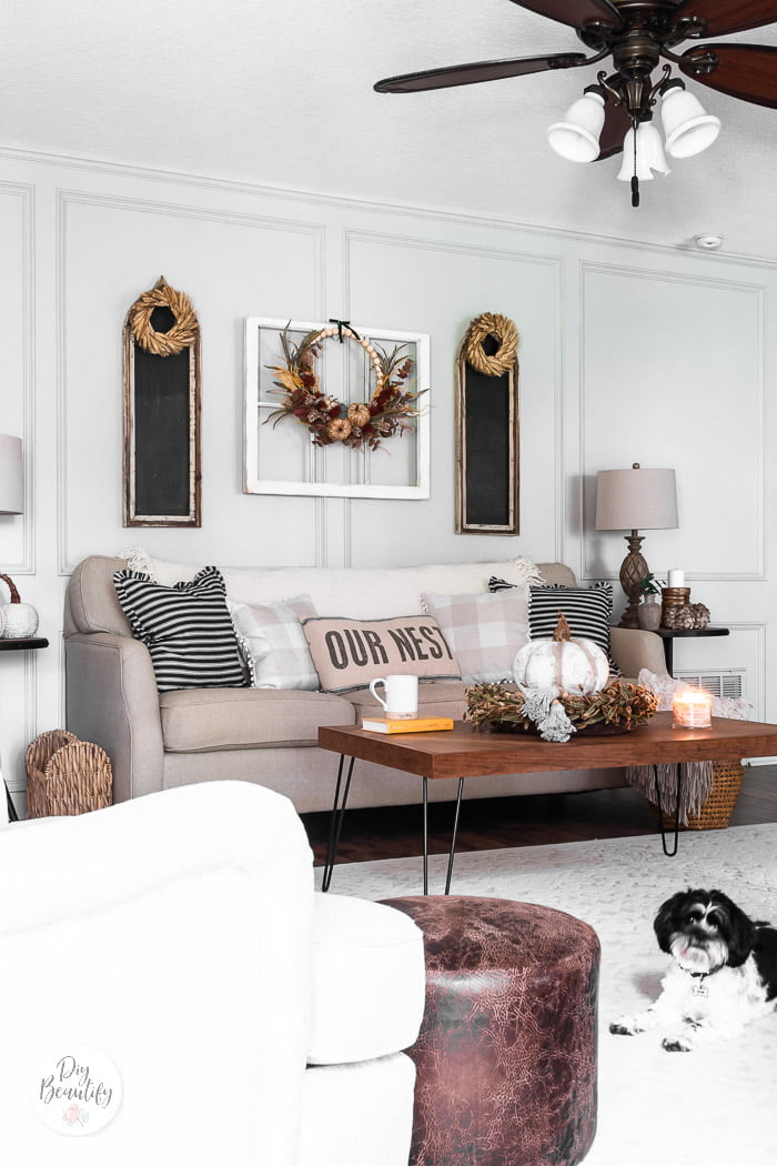 Neutral furnishings in living room warmed up with pillows, fall decor and puppy
