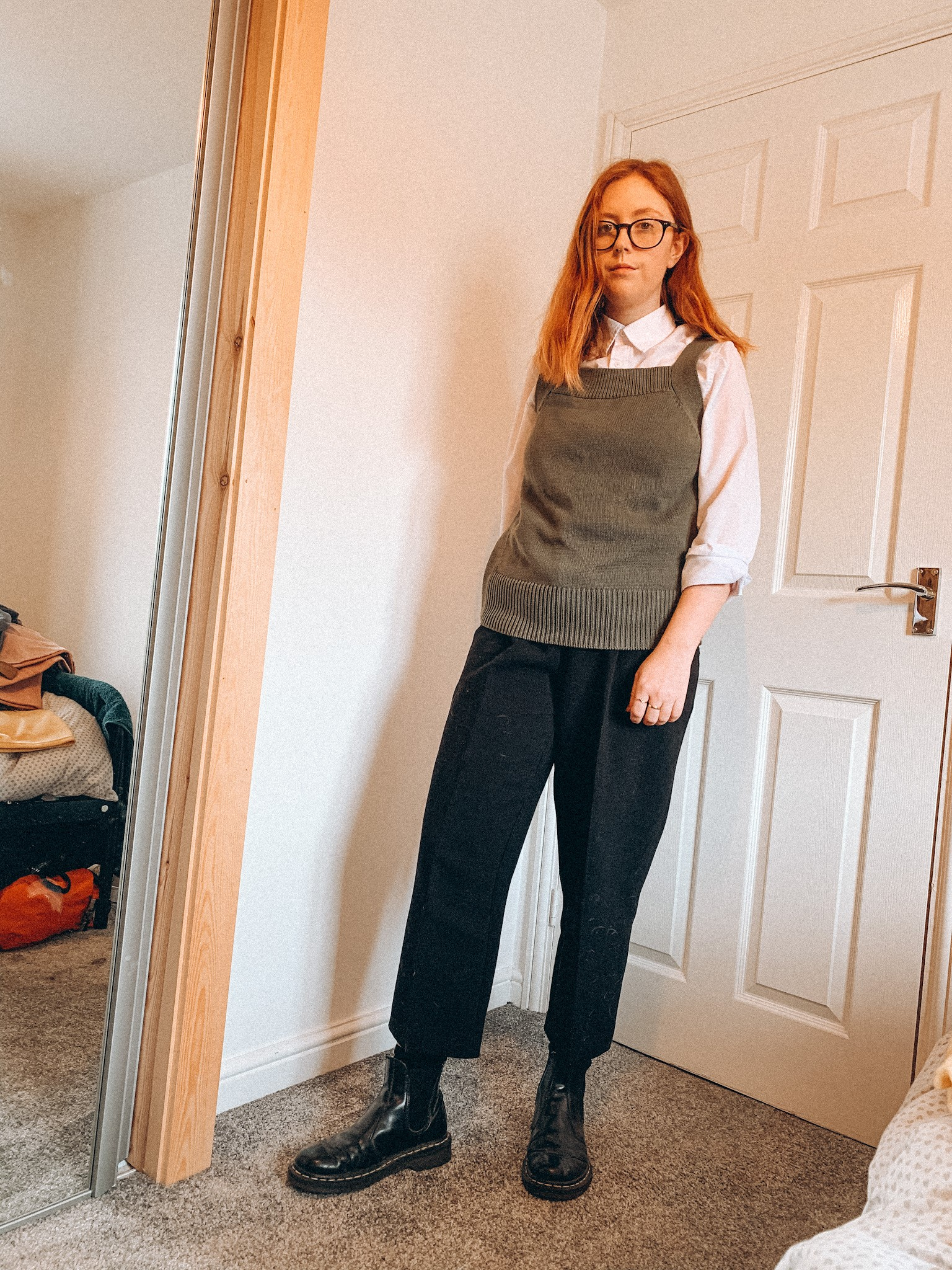 ginger haired woman wearing second hand shirt, knitted vest, black trousers