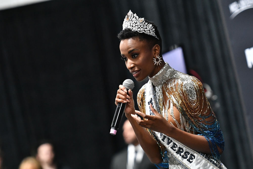 Miss Universe 2019 Zozibini Tunzi, of South Africa, is crowned onstage by Miss Universe 2018 Catriona Gray (R, in blue) at the 2019 Miss Universe Pageant at Tyler Perry Studios on December 08, 2019 in Atlanta, Georgia. (Photo by Paras Griffin/Getty Images)