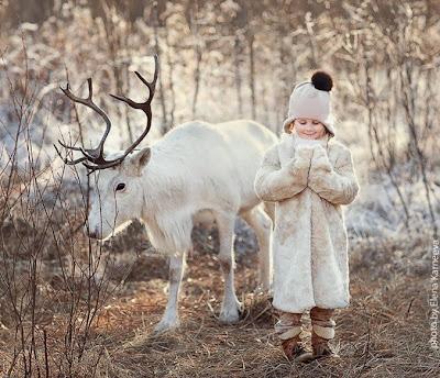 Niña y reno en la nieve
