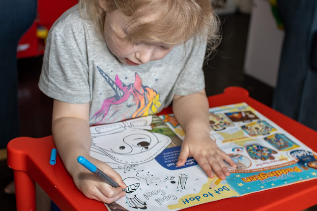 A 5 year old girl completing a dot to dot activity in a magazine.