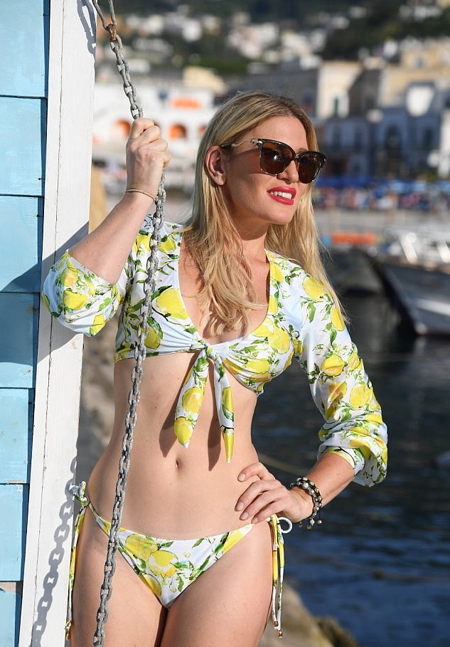 Hofit Golan shows off her enviable curves as she slips in lemon-embellished bikini and slinky one-piece