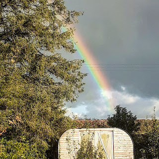 Bright rainbow in grey sky, strikes the curved roof of a large shed