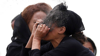 A family member of one of the victims pouring sand on her face
