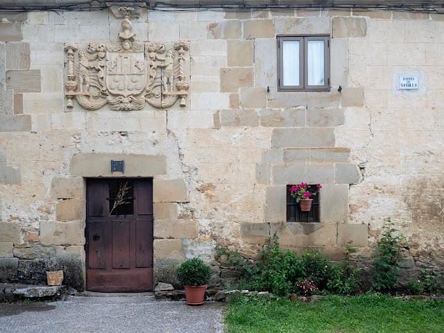 Fachada de casa medieval con escudo heráldico de piedra sobre la puerta y flores en la ventana