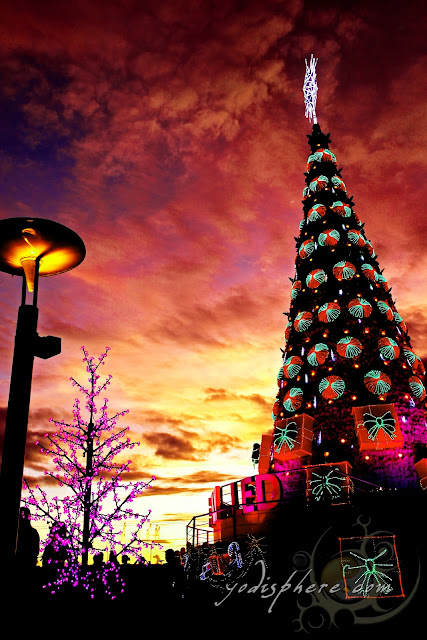 Colorful giant Christmas Tree against sunset at SM Mall of Asia, San Miguel by the Bay