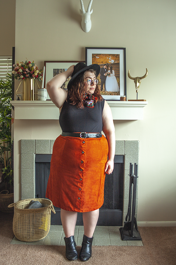Black wide burm hat, vintage brown and orange neck scarf, black mockneck sleevess top tucked into an orange midi skirt with black Chelsea boots.