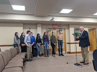 Town Council Chair Tom Mercer with proclamation recognizing the FHS student for their work on the plastic bag prohibition