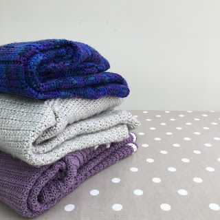 Stack of three crochet garments