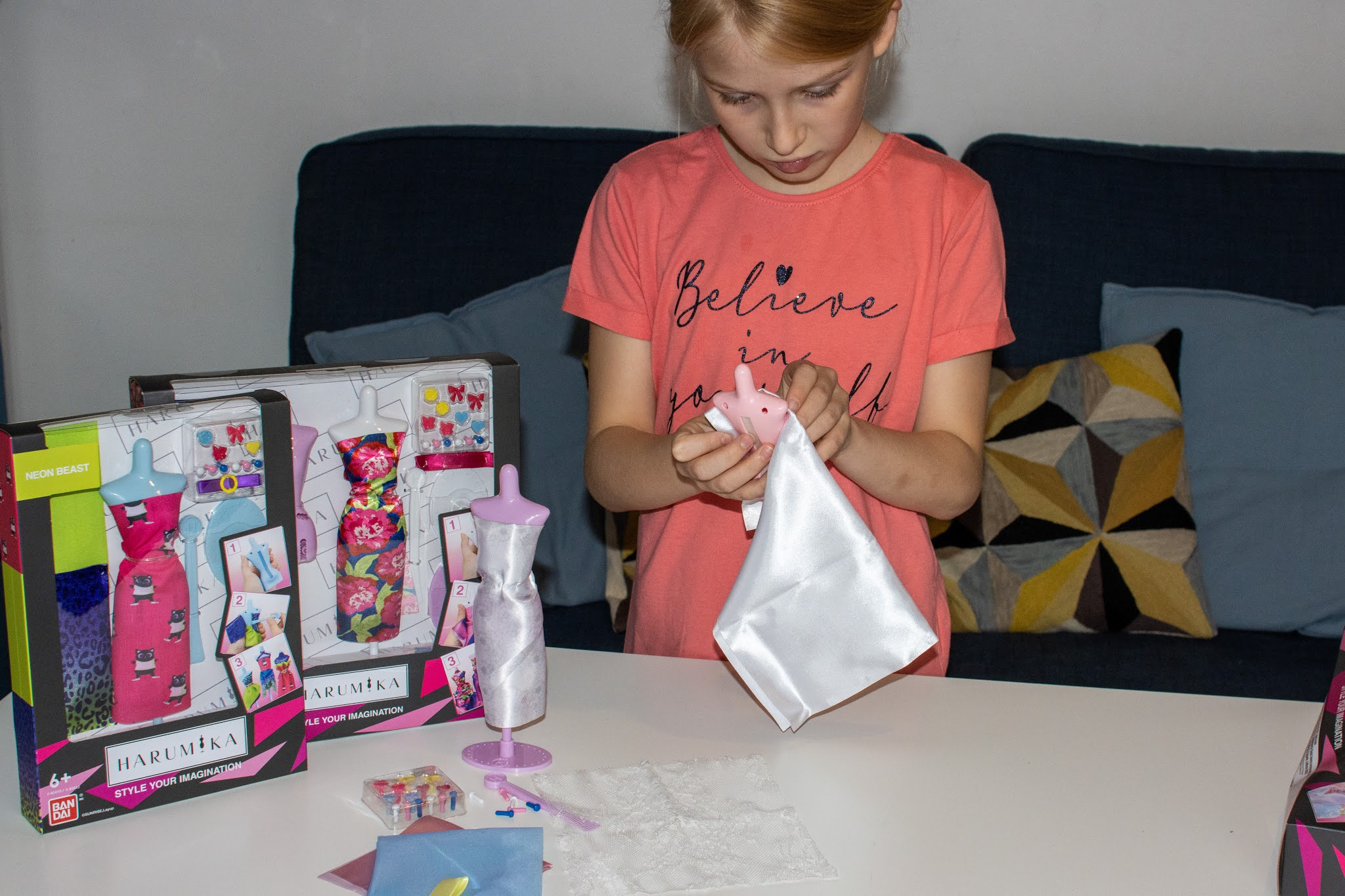 A 9 year old in a believe in yourself t-shirt wrapping white fabric around a toy doll size mannequin