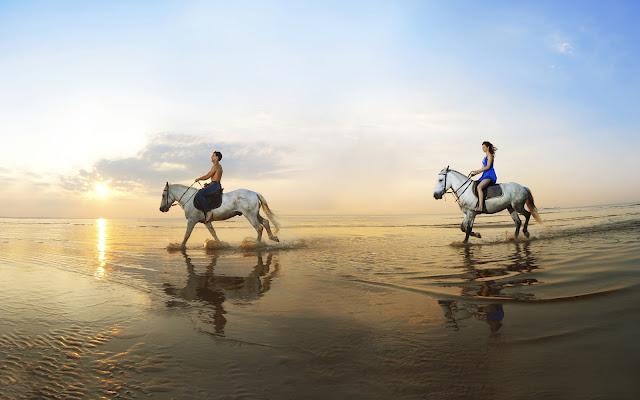 Paardrijden op het strand door het water van de zee